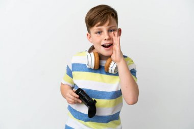 Little redhead boy holding a game pad isolated on white background shouting with mouth wide open