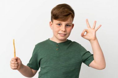 Little redhead boy holding a toothbrush isolated on white background showing ok sign with fingers