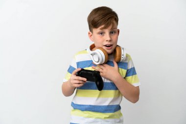 Little redhead boy holding a game pad isolated on white background surprised and shocked while looking right