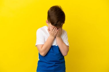 Little redhead boy isolated on yellow background with tired and sick expression