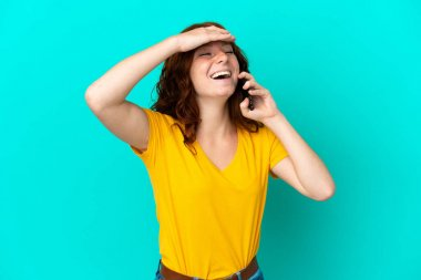 Teenager reddish woman using mobile phone isolated on blue background smiling a lot
