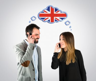 Couple talking to mobile over grey background.