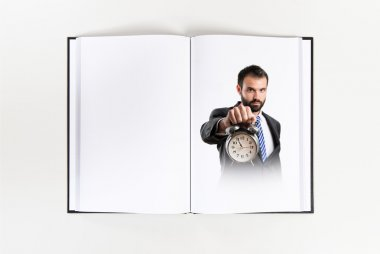 Young businessman holding an antique clock printed on book stock vector