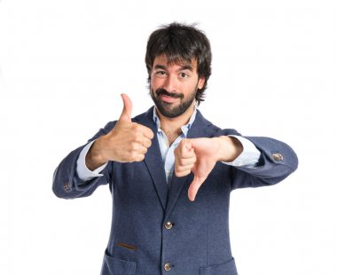 Handsome man making a good-bad sign over white background