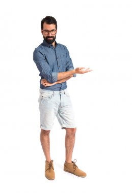 Young hipster man presenting something over white background