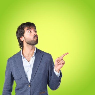 Businessman thinking over green background