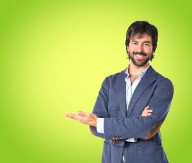 Businessman presenting something over green background