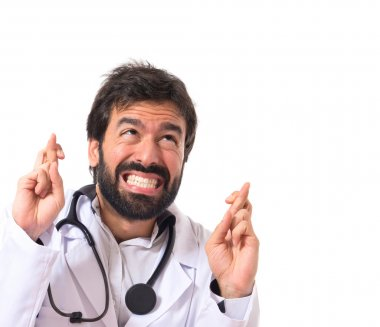 Doctor with his fingers crossing over white background