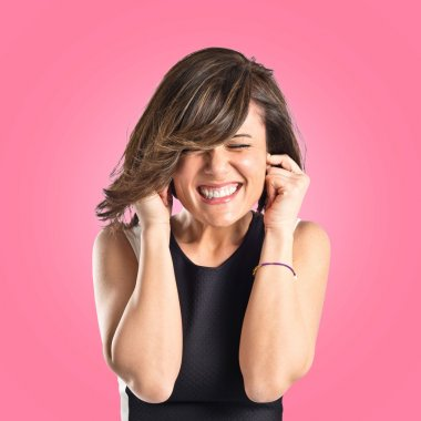 Young pretty woman covering her ears over pink background