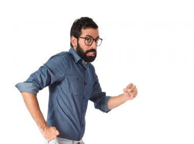 Young hipster man running fast over white background