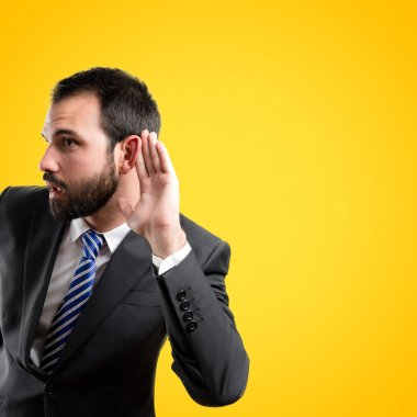 Young business man hearing something over yellow background
