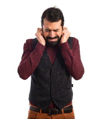 Man wearing waistcoat covering his ears