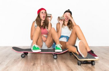 Friends with their skateboards talking through a tin phone