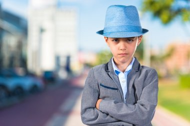 Sad child with his arms crossed wearing a blue hat