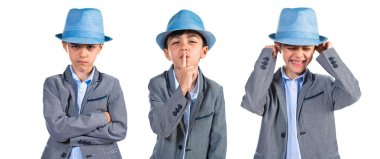Boy wearing blue hat making silence gesture