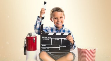 Kid with clapperboard and popcorns