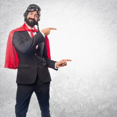 Super hero businessman pointing to the lateral
