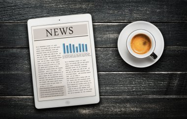 News article on digital tablet and coffee cup