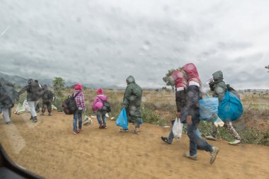 Refugees and migrants walking the dusty road