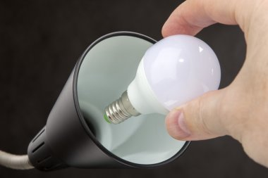 Installing LED lamp with lampshade Household lamps, black background.
