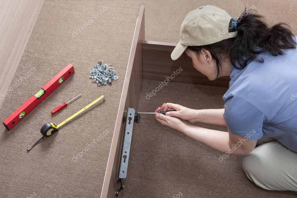 Woman housewife putting together assemble bed frame, using hand ...