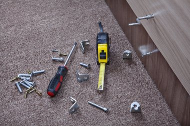 Steel fasteners, brackets and hand tools to install furniture.