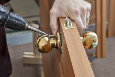Installation door knob with lock, woodworker screwed screw, using screwdriver.