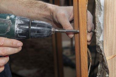 Carpenter fix jamb in doorway using a cordless drill electric screwdriver, close-up.