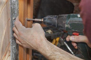 Woodworker screwed jamb in doorway using cordless drill electric screwdriver.
