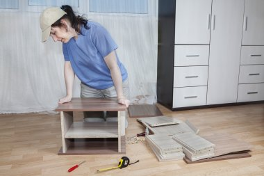 Assemble furniture, carpenter apply glue and clamp two boards together.