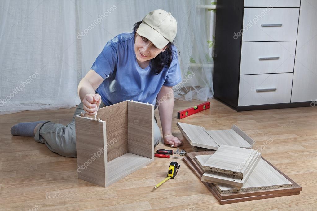 montage de meubles, femme monte boîte de carton gris, avec de la