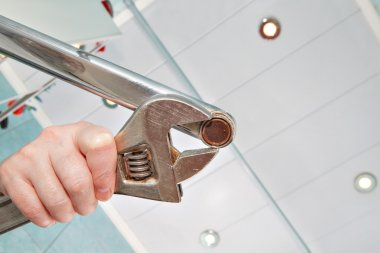 Remove old aerator from faucet with an adjustable wrench, close-up.