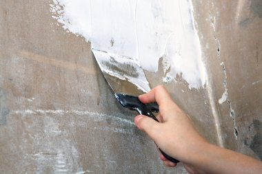 Work plasterer, dirty spatula in hand painter, close-up.