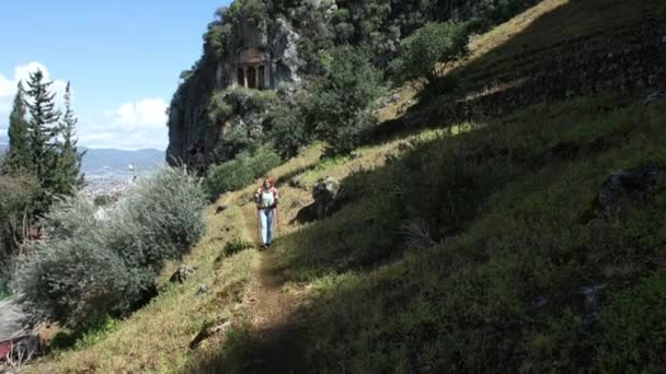 Famous places of resort town of Fethiye in Turkey, Lycian tombs, young woman walks along slope of mountain while walking near monument.