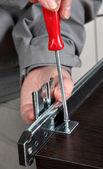 Photo Installing  track drawer slide rail, screwing screw manual screwdriver.