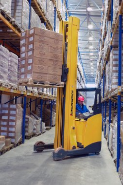 Yellow pedestrian stacker lifts pallet with boxes on the shelves