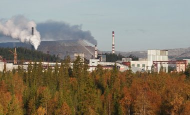 Mining plant in Russia, autumnal forest, factory buildings, slag heaps.