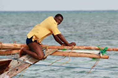 Black African fisherman, untie rigging sailing fishing boat.