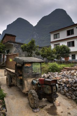 Battered ancient farmer tractor stands in peasant village, Guang