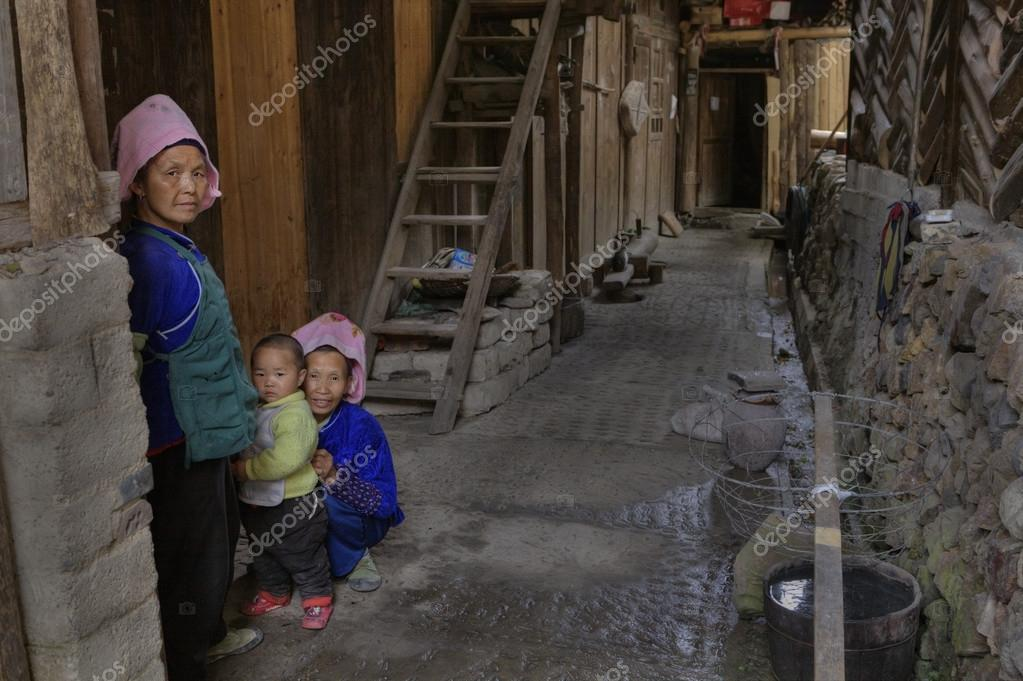 ... Guizhou Province, China - april 17, 2010: Rural Wooden Peasant Farmer  House Yard, Two mature Asian woman and a child, a little boy, about 2 years  old.