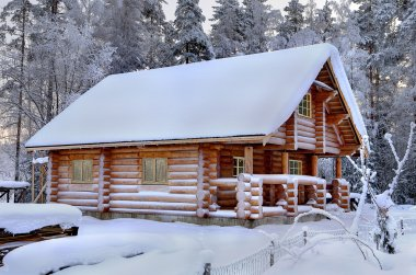 New wooden Russian sauna in a snowy winter forest, sunny day.