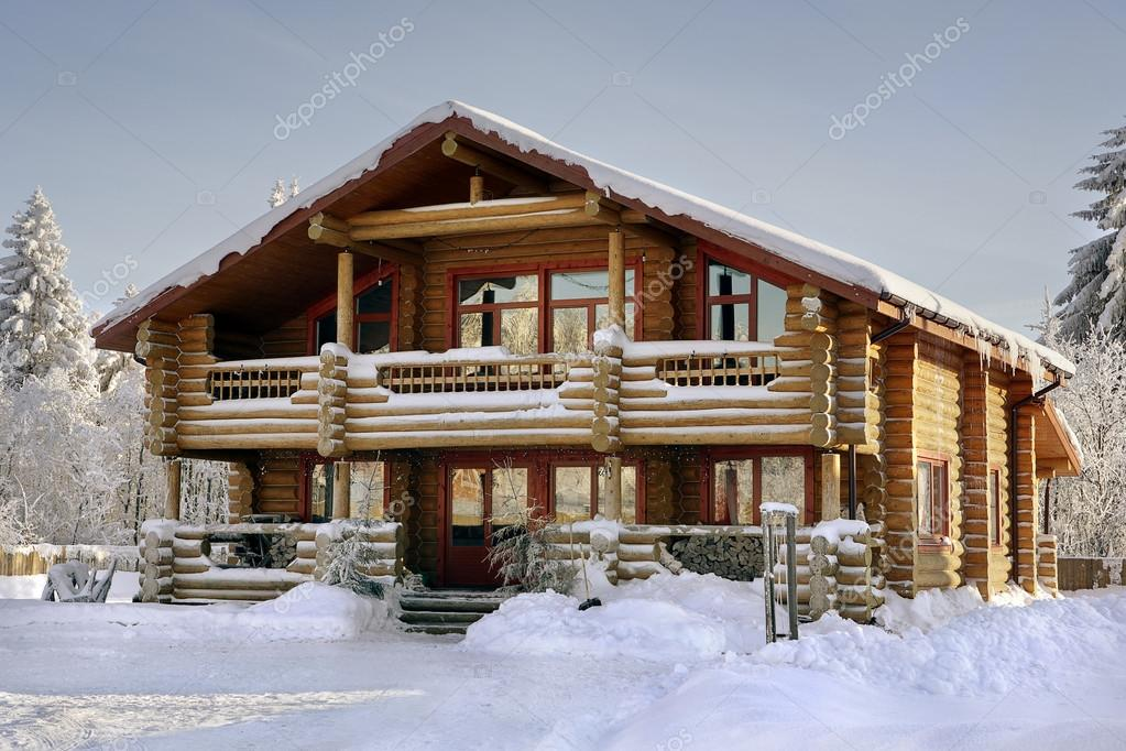 Log house covered in snow during winter.