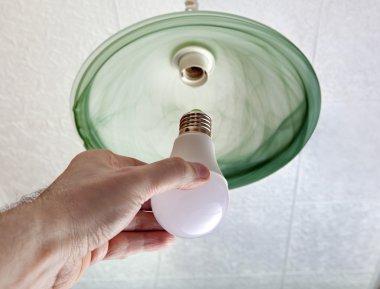 Installing LED light bulb in ceiling light, hand holding lamp.