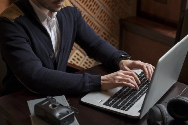 Mans hands typing on laptop at workplace