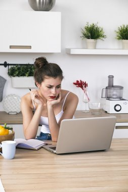 Portrait of housewife at table with laptop in kitchen
