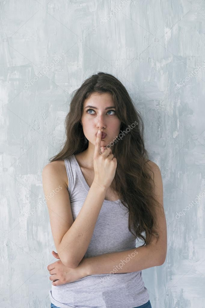 Attractive brunette thinking with finger on lips