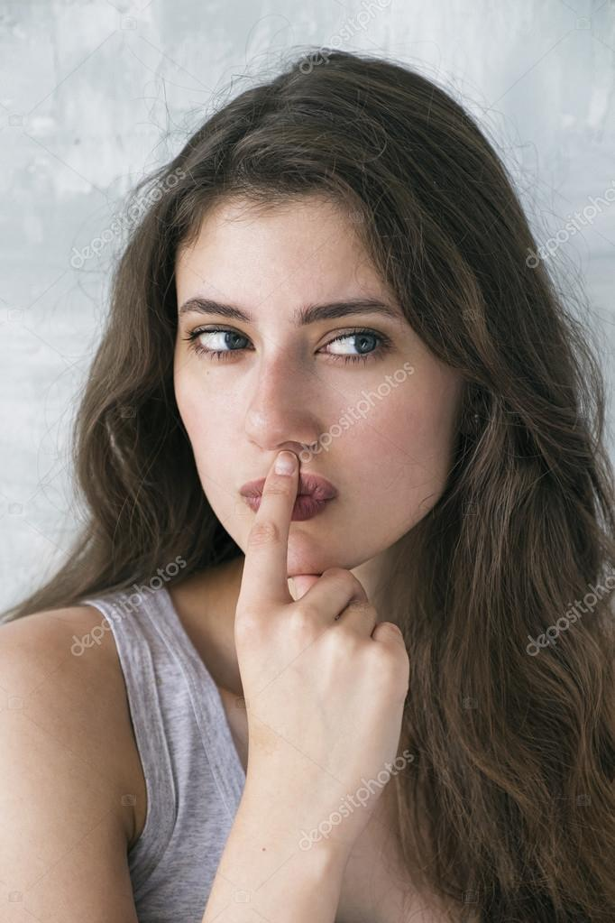 Thinking woman looking away with finger on lips