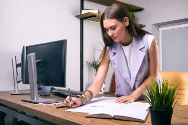 Brunette woman taking notes on documents