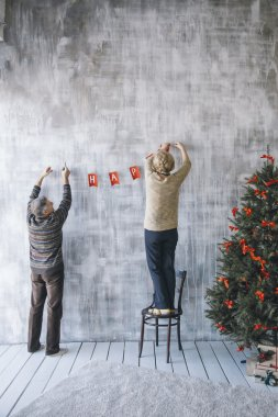 Two people decorating the wall