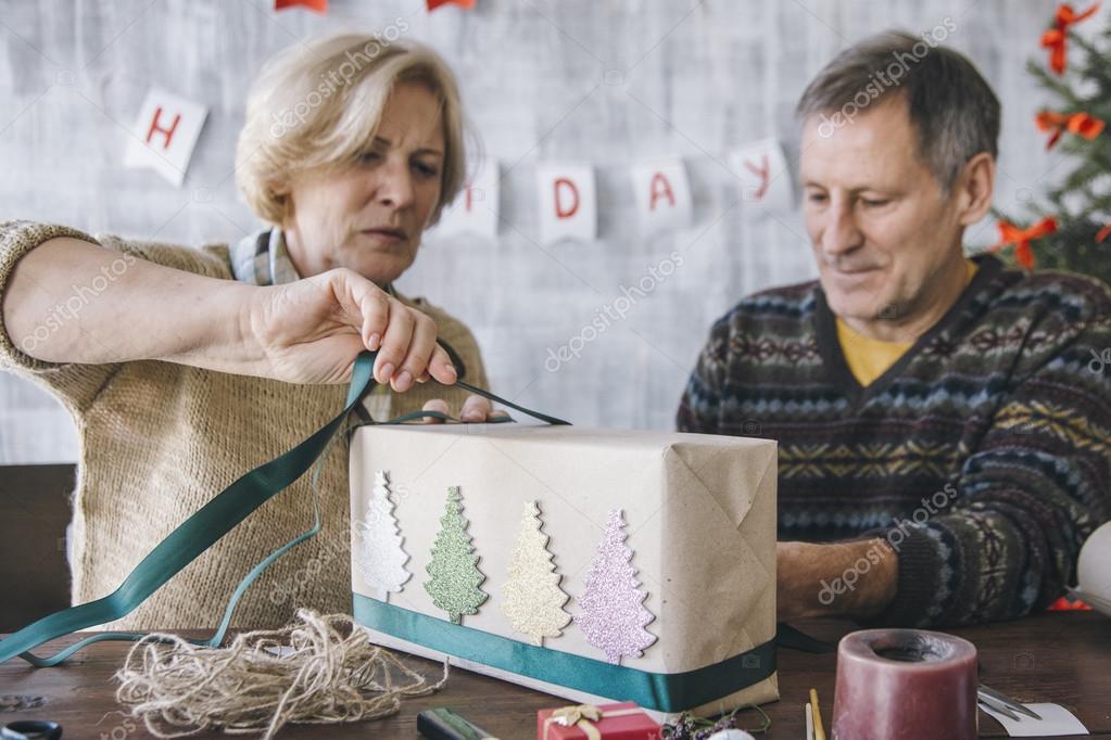 Älteres Ehepaar schmücken das Weihnachtsgeschenk — Stockfoto ...